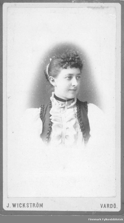 Portrett av ukjent kvinne. Hun er kledt i hvit bluse og en mørk vest. I halsen har hun et bånd med et kors. På blusen har hun en brosje. I håret har hun et bånd