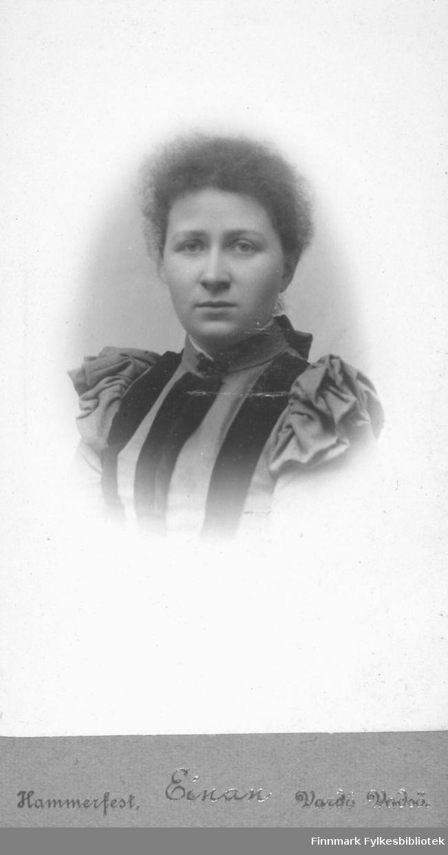Portrett av ukjent kvinne. Hun er kledt i en mørk kjole eller bluse med puffermer