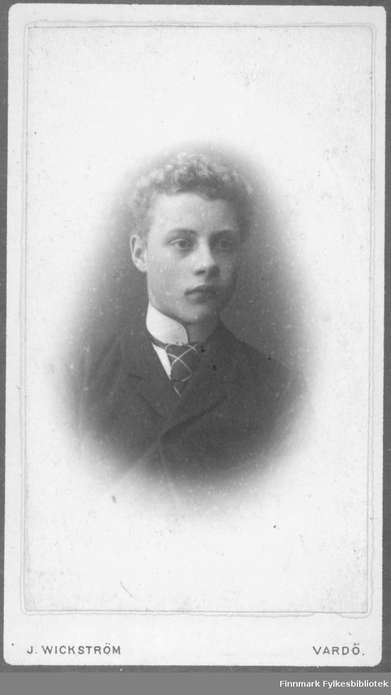 Portrett av en ukjent ung mann. Han er kledt i en mørk jakke og hvit skjorte. I halsen har han et mørkt slips med lyse striper