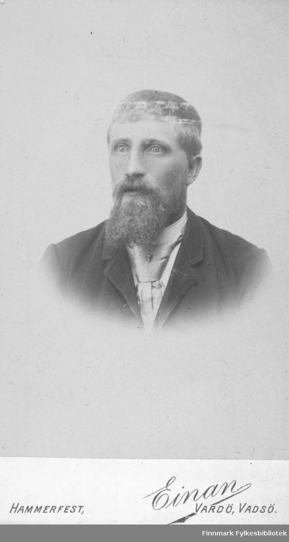 Portrett av en ukjent mann med bart og skjegg. Han er kledt i en mørk jakke og hvit skjorte. I halsen har han et silkeslips med et lite smykke