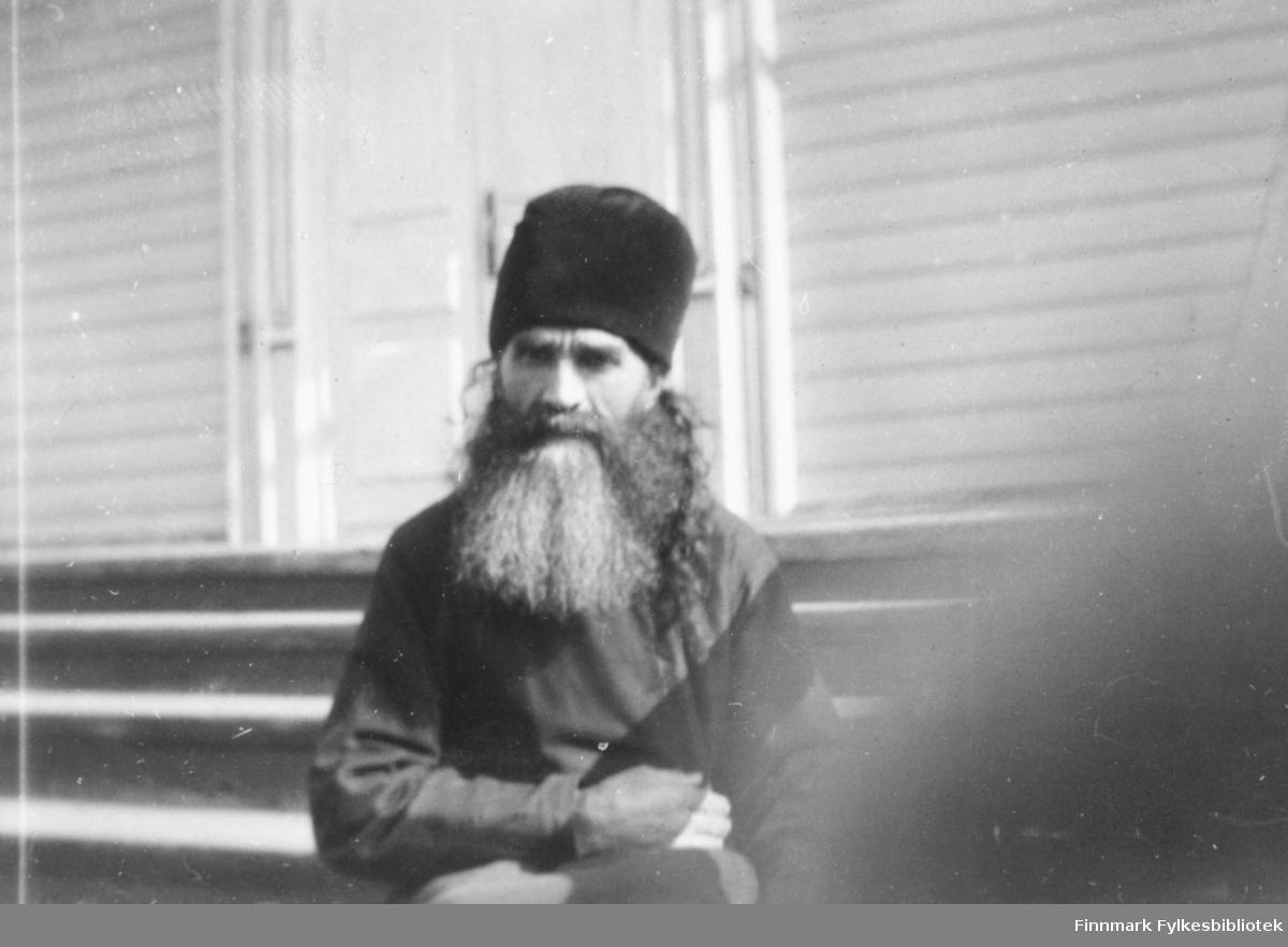 Fotografi av en mann med langt skjegg. Han er kledt i en mørk kjortel. På hodet har han en høy mørk lue. Han sitter på en trapp foran en lys trebygning, som har en hvit bred ytterdør. Mannen er muligens en munk