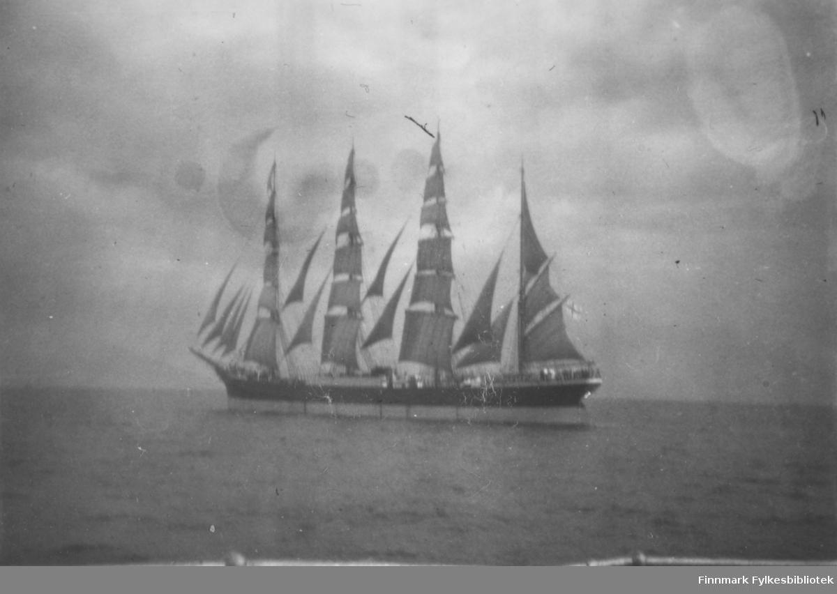 Fotografi av en seilskute. Den har fire høye master med  seil. I mellom mastene og i baugen er det også flere små seil festet til mastene. Den øverste delen av skroget er mørkt. Delen som er nærmest vannet er lyst