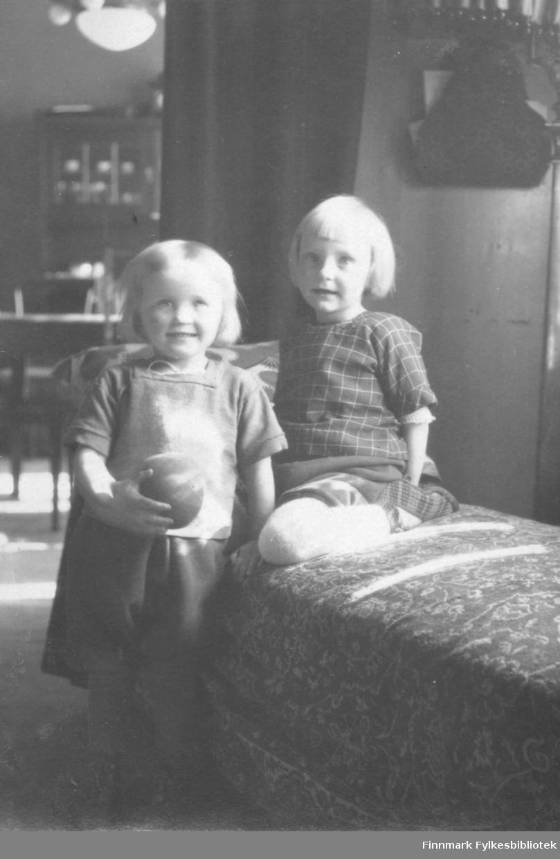 Fotografi av Liv og Gerd Vibe Jacobsen fra Bergen. De er døtre til August Magnus Jacobsen fra Vardø og hustru Solveig Johannessen Jacobsen fra Bergen. Gerd sitter på en divan og Liv står ved siden av og holder en ball. Jentene er kledt i skjorte og skjørt. I bakgrunnen ser man et vitrineskap og deler av et bord og en stol. Det henger en lampe i taket