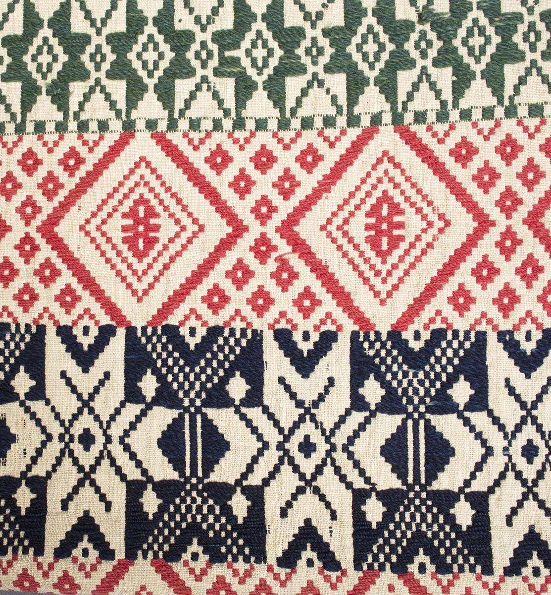 """Täcke vävt i opphämta. Randig mittspegel med rött, mörkblått eller grönt mönster på ljus tuskaftsbotten i halvblekt linne. Bårder av stjärnor och rutor, rutraderna i rött, stjärnraderna varannnan grön, varannan mörkblå. Grön mönsterbård i kortsidorna med spetsuddiga stjärnor, ca 80 mm bred. Bård i långsidorna i mörkblått, 40 mm bred. Mellan bården i långsidorna och mittspegeln löper en 8 mm smal rand i bottenfärgen. Täcket är ihopsytt på mitten av två delar med färgpassning trots halvornas olika längd. Mittsömmen är sydd med efterstygn i 2-trådigt s-tvinnat lingarn. Smal fåll i kortsidorna, stadkanter i långsidorna.Varp i halvblekt 1-trådigt z-spunnet lingarn, 14 trådar/cm.Botteninslag samma som varpgarnet, 10 inslag/cm.Mönsterinslag i 2-trådigt z-tvinnat ullgarn, 10 inslag/cm.Lappad med en liten tygbit i stadkanten 20x70 mm, mönstret är där inbroderat med blått bomullsgarn.Märkt på baksidan med påsydd tyglapp med texten: """"Landstinget n° 127 a Ljunits."""" Intill finns rester av en fastsydd pappersetikett från Malmöhus läns Hemslöjdsmagasin, Malmö. Täcket är också märkt med ett fastnästat bomullsband med texten: """"8356 MALSÄKR. 6/10""""."""