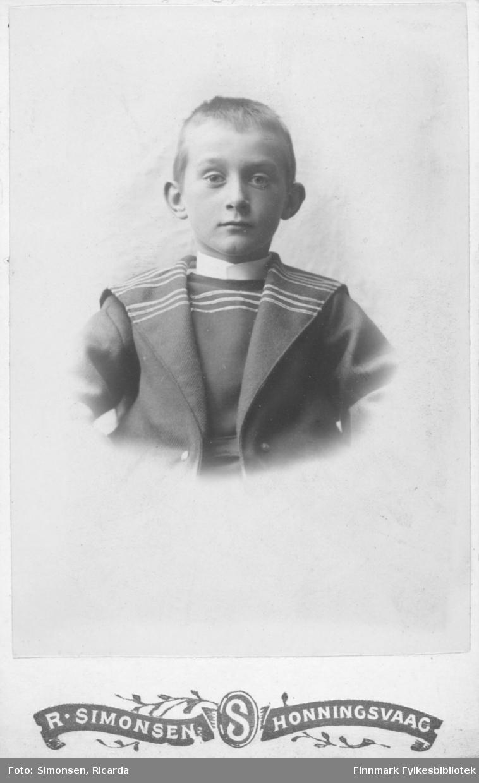 Portrett av en gutt barn kledd i en mørk dress med lue.  Albumet med bildet kommer fra Ekkerøy, kanskje han kommer derfra.
