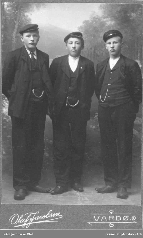 Portrett av tre 3 unge menn gutter kledd i mørke dresser alle har luer hatter hvite skjorter en har slips alle tre har lommeur i lenker. Studio ateliere malt bakgrunn.  Albumet med bildet kommer fra Ekkerøy, kanskje de kommer derfra.