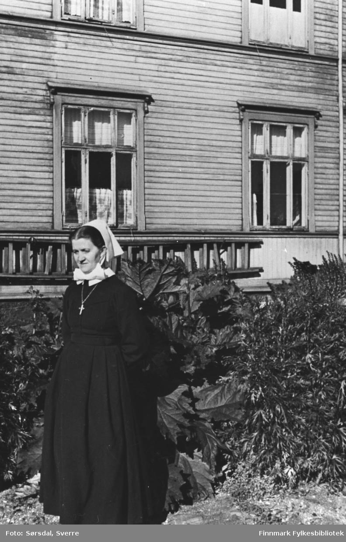 Bildet av oversøster Martha Eckmann i uniform. Står ute foran Vardø sykehus.