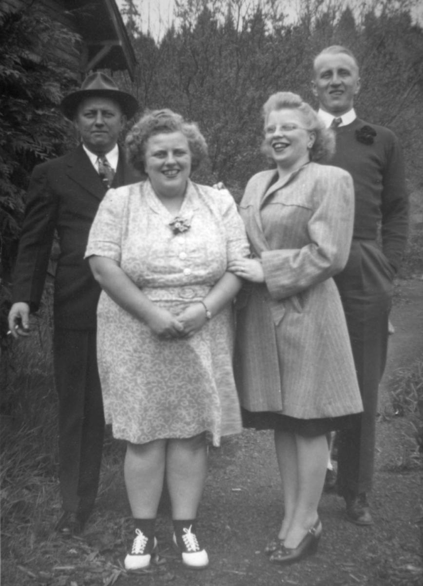 Et gruppebilde av to kvinner og to menn. Personene er fra venstre: Fred Ojala, Wilma Ojala, Elma Ojala Bailey (?) og  Hannes Ojala. Mennene er kledd i dress: slips, jakke og bukse. Fred har på seg en hatt. Wilma er kledd i kjole, sokker og sko. Hun har festet blomster på halsstykket til kjolen. Elma har på seg en stripete kåpe og høyhælte sko. Fred holder en sigarett mellom fingrene. Bildet er tatt i Laden(?)21.april 1946.