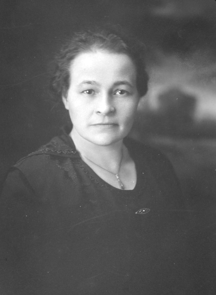 Portrett av Elmine Eugenie Korbi tatt i Milwaukee, USA. Hun er kledd i mørk overdel og har et smykke rundt halsen. Ugift. Emigrerte til Milwaukee i 1906, hvor hun bl.a. jobbet som tjenestepike. Bodde sammen med sin søster, Nanna, i Milwaukee.