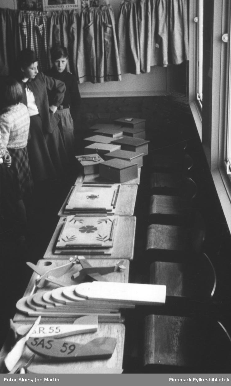 Utstilling av produkter laget av fjerdeklassingene i sløyd- og håndarbeidstimene, Øksfjord barneskole 1954. Fra venstre: Gunnar Rydheim (i kofte), Hildegunn Hansen (med ryggen til), Evy-Ann Larsen (seinere fylkesordfører), Ingolf Bye