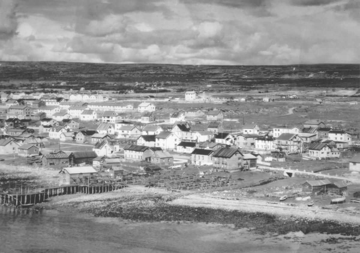 Oversiktsbilde fra Yttrebyen i Vadsø i 50-tallet. Grenreisningshusene står i rekke og rad. Bildet er tatt fra sjøen mot bebyggelsen.  Landhuselva og Hvistendalsgate i forgrunnen.