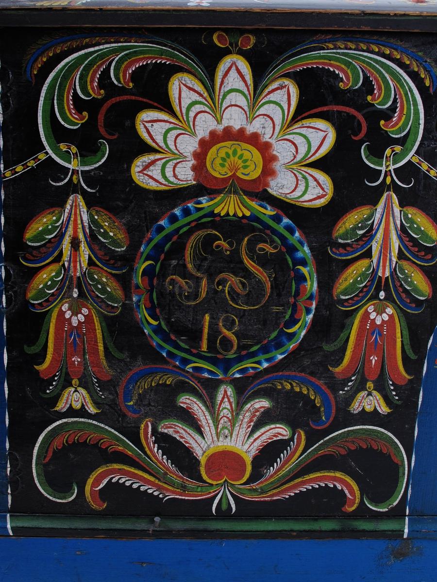 """Rosemaling på blå bunn.   På de svarte felter symmetrisk Agder-maling i grønt, hvitt, rødt og gult.  Forsiden med sirkelrunde navnefelt hvori """"GS-DM"""" over """"18-63"""".  Kortsidene er nøttetresmalt i rødbrunt"""