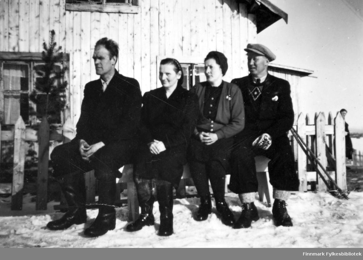 Fotografi av to menn og en kvinne som sitter ute foran et gjerde på en benk. Fra venstre: Magnus og Helga Stenbakk, Henrika og Johan Sotkajærvi. Det er et to etasjes trehus i bakgrunnen. Helt til høyre i bildet er det en person. Det ligger snø på bakken, og det står et par ski mot gjerdet. Magnus og Helga er begge kledt i mørke klær, og på føttene har de høye støvler. Henrika og Johan er kledt i turklær og sko