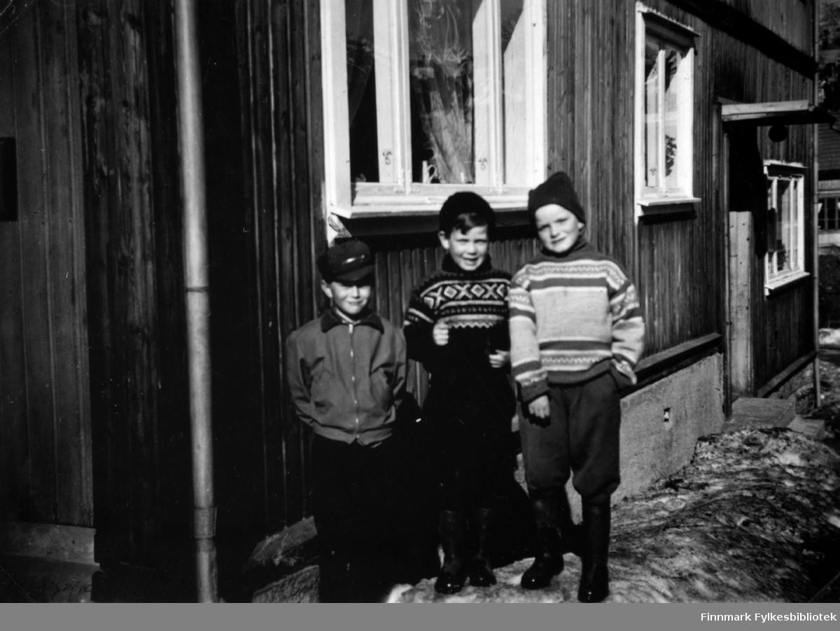 Fotografi av tre ukjente gutter som står utenfor et trehus. Gutten i midten har på seg Mariusgenser.