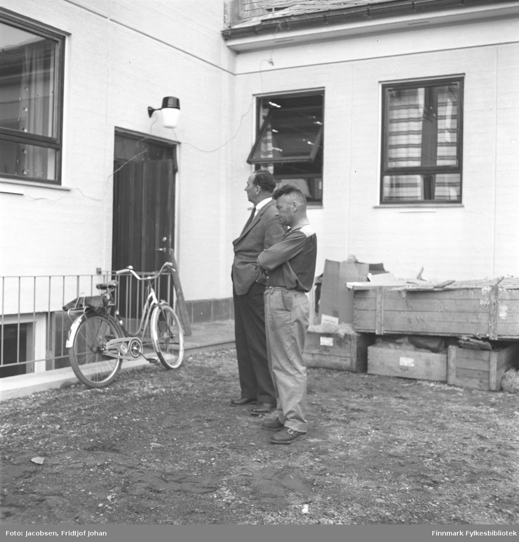 Distriktssjef Sigurd Torgersen og Leif Erntsen står i bakgården til Post- og Televerkets bygg i Bossekop i Alta.