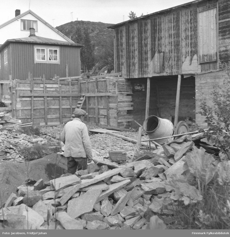 Arne Nakken murer på hytta til Fridtjof Jacobsen i Bjørkåsen i Rypefjord. Nakkens hus ses oppe til venstre på bildet.