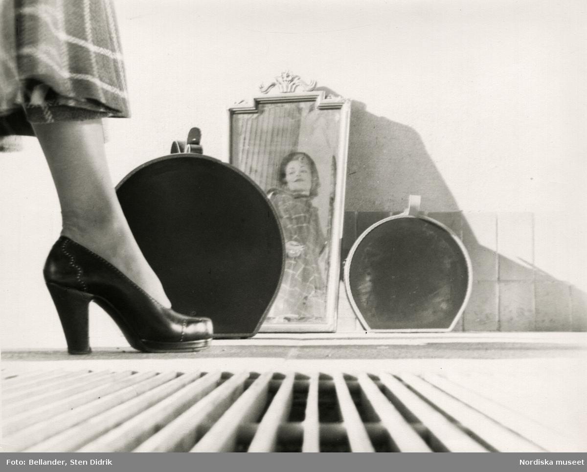 Kvinna i rutig kappa och pumps speglar sig i spegel på gatan. Två resväskor och en brunn bredvid.