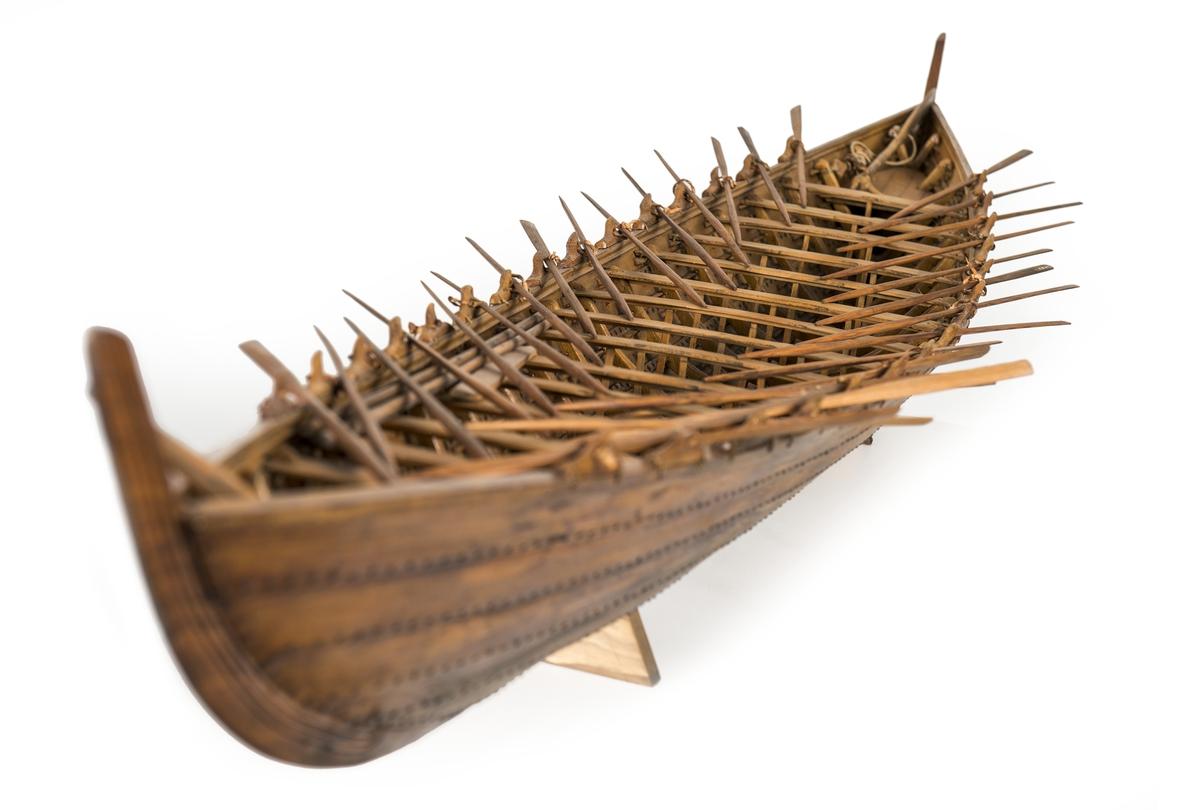 """Båtmodell av """"Nydambåten"""", hel spantbyggd av trä. Fartyget är klinkbyggt, 5 bordgångar på var sida, sammannitad med metallnaglar. 19 spant, 16 tofter ooh 15 par åror av varierande längd. Årtullar med läderremmar, en styråra, 4 bärlingar, ett öskar, en dyvecka samt tvenne surrningsbrokar av trä."""