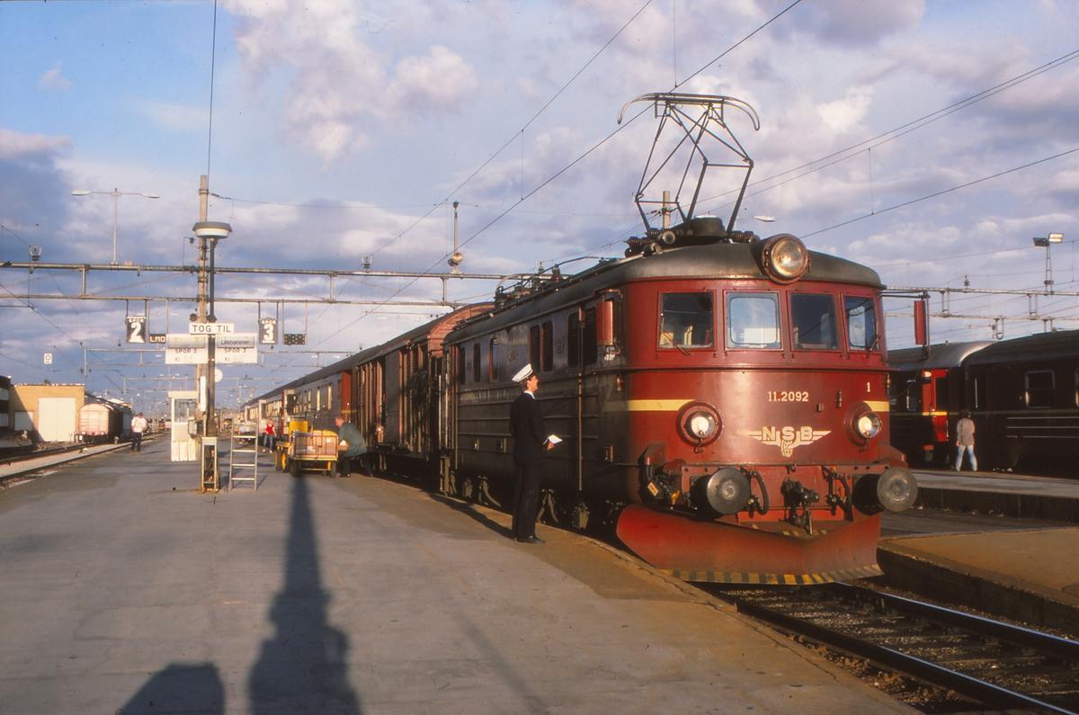 Persontog 341 Oslo - Lillehammer på Hamar stasjon med NSB elektrisk lokomotiv El 11 2092. Togfører og lokomotivfører konfererer mens reisegods og ekspressgods losses og lastes.