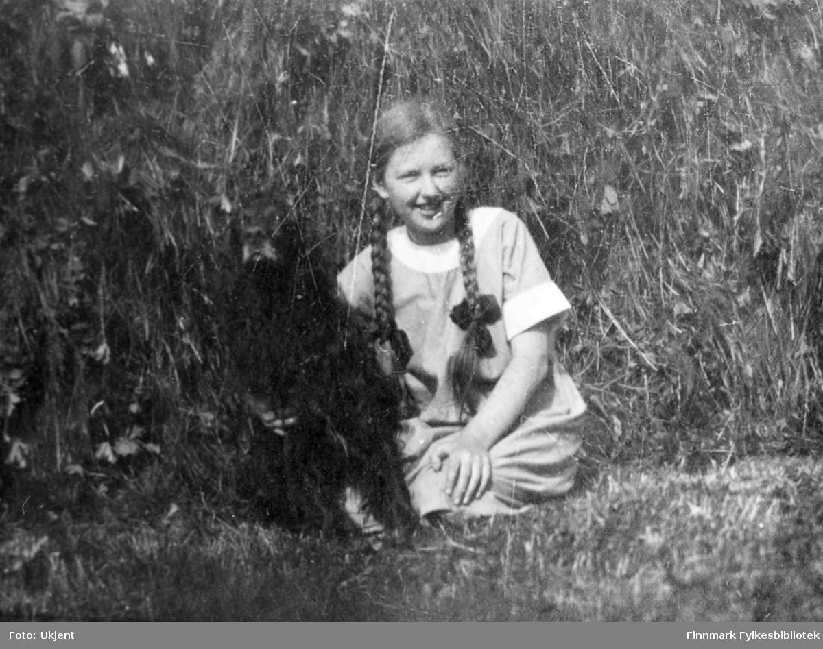 Bildet trolig tatt Sommeren 1923 i Jarfjord. Piken på bildet er Aagot Bertelsen, ved siden av henne sitter en mørk hund som trolig er familiehunden 'Tussemann'. Aagot har på seg en kjole og har flettet hår med sløyfer. Hun sitter på bakken og holder rundt hunden.