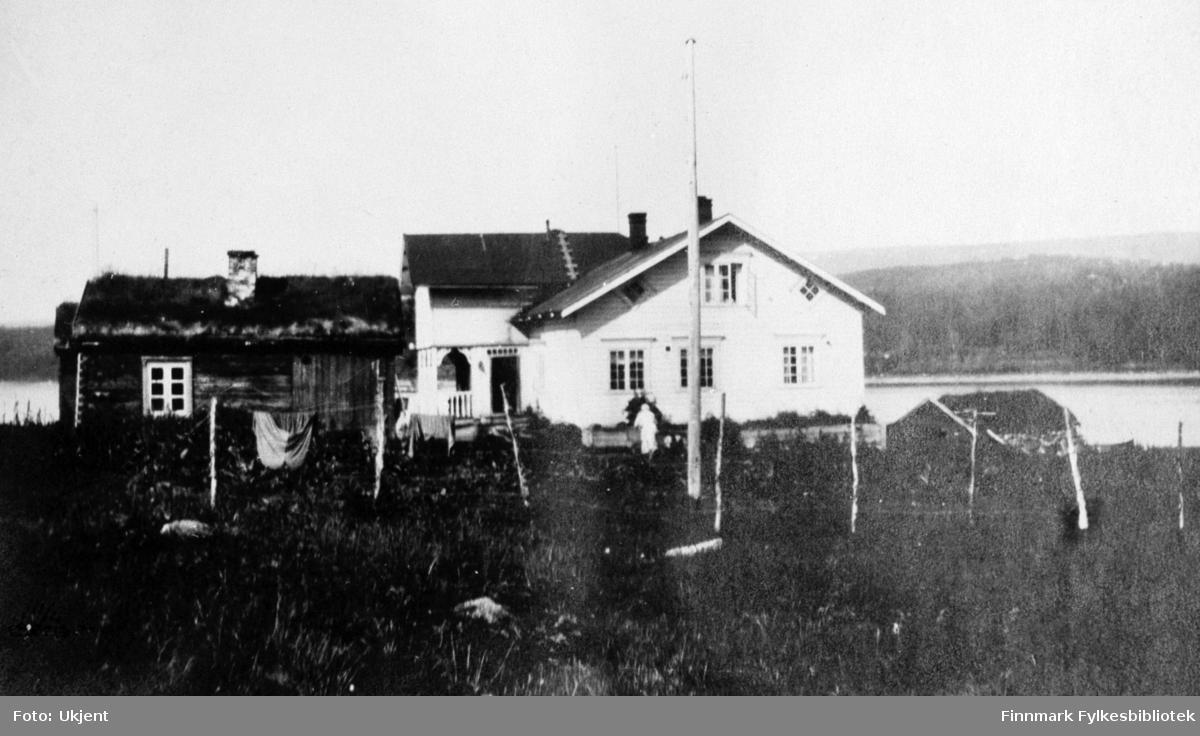 Bildet er tatt av gården Strømsnes i Jarfjord sommeren 1924. På bilde kan man se selve hovedhuset og et lite uthus med torvtak. På begge husene er det mulig å se skorsteiner og vindu. Vinduene har gardiner på hovedhuset og man kan se en liten stige på taket som fører opp. En ukjent person står ved siden av huset. Bak uthuset kan man se at det tørkes klær på line og det er satt opp et gjerde langs tomten. Helt til høyre kan man se taket på et mindre hus. Nærmest fotografen kan man se en flaggstang. I Bakgrunnen ser man havet og fjell.