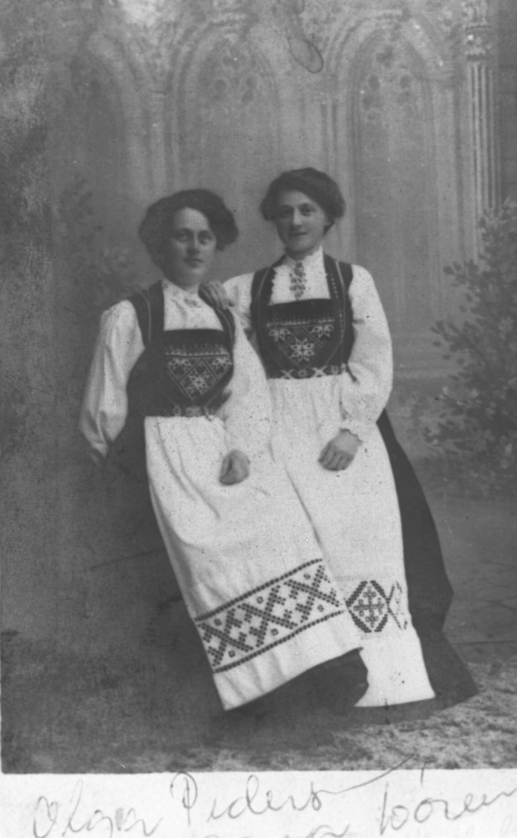 Kabinettportrett av to unge kvinner i bunader. Fra venstre: Olga Marie Pedersen og Lise Hendriksen. Disse unge damene er ca 16-20 år gamle. Bildet er opprinnelig kopiert til postkortform (postkortmarkering på baksiden) men senere klep til og passe in i visitkortalbumet.