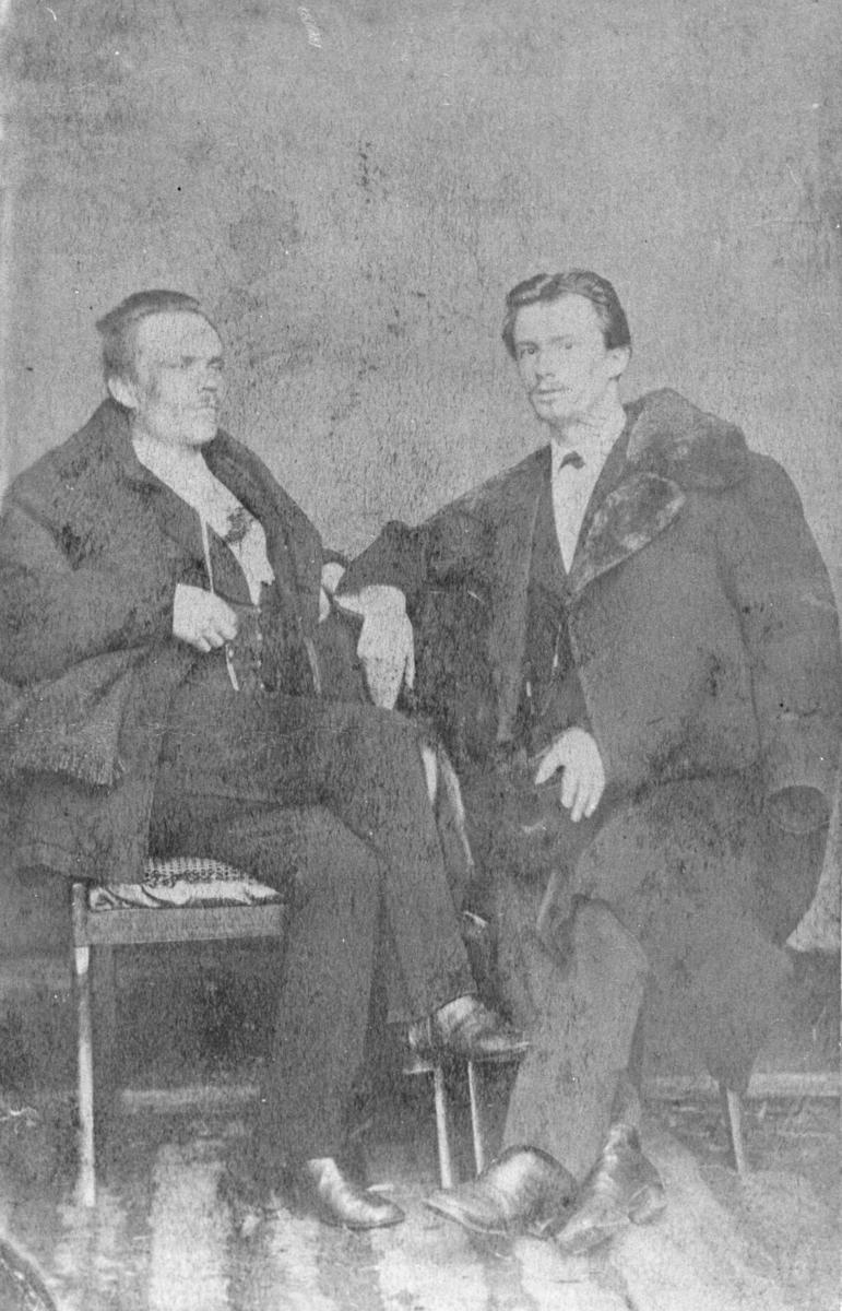 Portrett av to menn. Mennene er vel kledd i dress og lange jakker med pelskrager. Herrene sitter på stoler, den ene av dem har en hatt på handen. Bildet er gammelt, ca 1855-60, og montert på tynt kartong