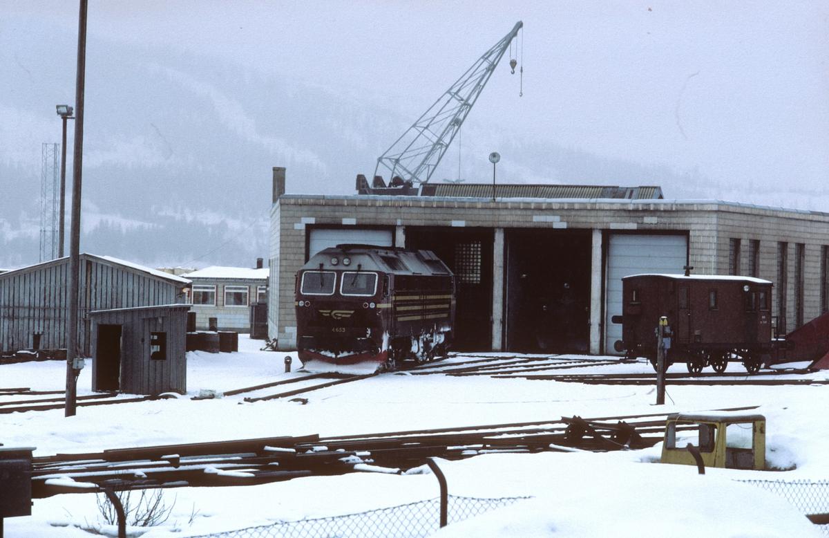Lokomotivstall og svingskive i Mo i Rana med et dieselelektrisk lokomotiv type Di 4. I bakgrunnen en kran tilhørende Mo havnevesen. Til høyre en sporrenser.