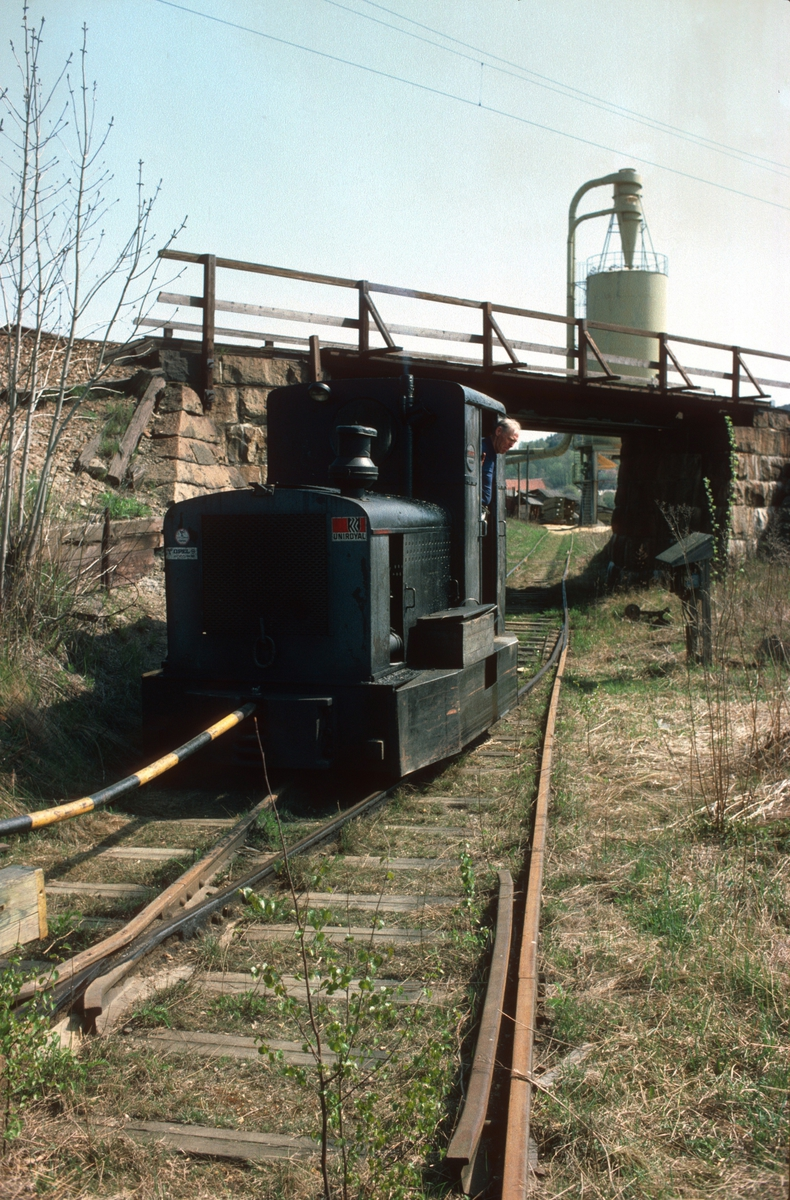 Tog på bruksbanen til Saugbrugs, Halden, (Norske Skog Saugbrugs). Ved undergang under Østfoldbanen. Normalspor. Diesellokomotiv Deutz type OMZ122F, byggenummer 46499 - bygget 1942. Opprinnelig 600mm sporvidde.