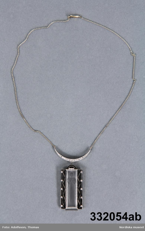 Luciahängsmycke från år 1950 tillverkad av 18K-vitguld, bergkristaller och diamanter. Hänget är 3,5 cm långt och i mitten av hänget finns en utskuren Luciafigur i slipad bergkristall. Figuren har långt hår (knälängd) och håller ett levande ljus i sin högra hand. Luciafiguren är klädd i en lång och enkel klänning utan ärmar och är barfota. Tretton små diamanter är placerade runt omkring bergkristallet--fem på varje sida och tre ovanför. /Petrine Knight, 2014-06-11