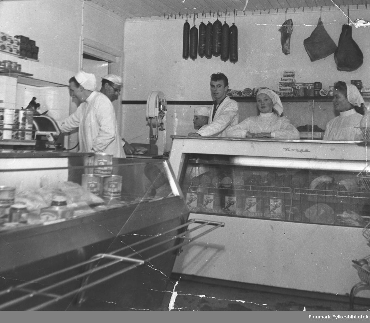 Fiskematforretning i Kjøllefjord, ca. 1962. Mannen med briller er innehaveren Edward Lund. Edwards kone Emmy står til venstre på bildet ved siden av Edward. De fire andre er fra venstre: Nils-Johan Lund, Even Herman Lund, Liv Lyngedal og Sigrunn Pedersen.