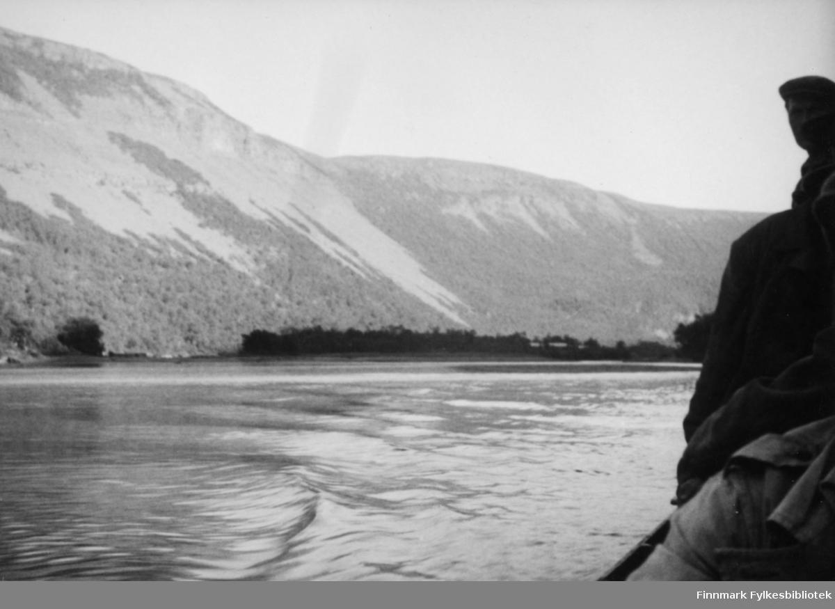 Altaelva trolig tatt fra en elvebåt. Til høyre ser vi siluetten av et eller to mennesker. I bakgrunnen ser vi en dalside og øyer i elva med tett vegetasjon