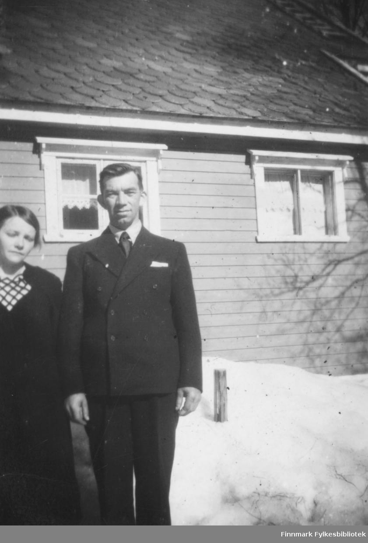Magna og Kristian Wisløff. Magna kledd i mørk kjole og Kristian i svart dress. De står utenfor noe som trolig er et bolighus. Til venstre ser vi snø og skyggen av et tre.