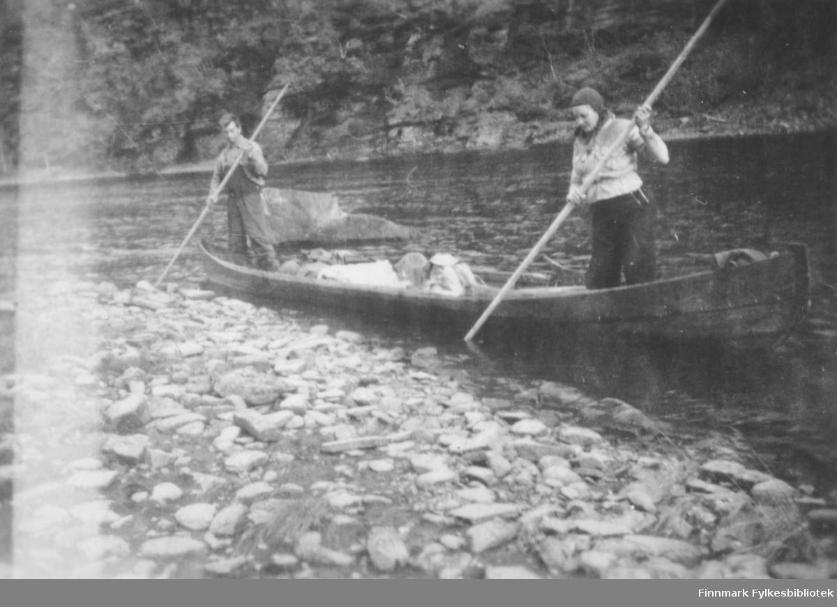 Elvebåtstaking på Altaelva. Kristian og Magna Wisløff står i hver sin ende av en elvebåt og ser ut til å skyve fra land. I bakgrunnen ser vi elva og en bratt dalside. Ca.1938-39.