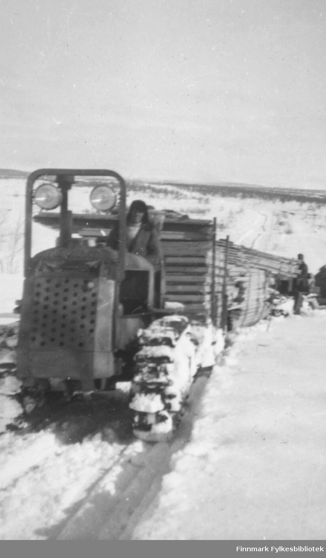 Gjenreisningen av Finnmark rett etter frigjøringen. Frakt av utstyr og materiale fra Alta til Kautokeino. Beltevognstraktor frakter store lass med tømmerbord. På noen av bildene ser vi føreren av traktoren og andre arbeidsfolk. Området er snødekt og flatt, typisk for Finnmarksvidda: serien inneholder bildene: 06002-052, 06002-053, 06002-055, 06002-056, 06002-057, 06002-058. Ca.1945-50.
