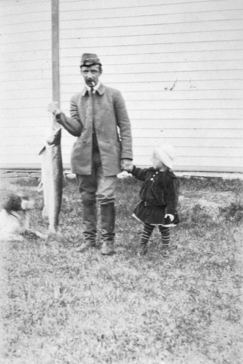 Lauritz Lassen Brodtkorb holder en stor laks i den ene hånden og en liten jente i den andre. Han har på seg en lang jakke, bukser, lue og støvler og en røyk i munnen. En hund ligger ved siden av han. Jenta har på seg en kjole, hatt og stripede sokker. Et hus med grunnmur i bakgrunnen.