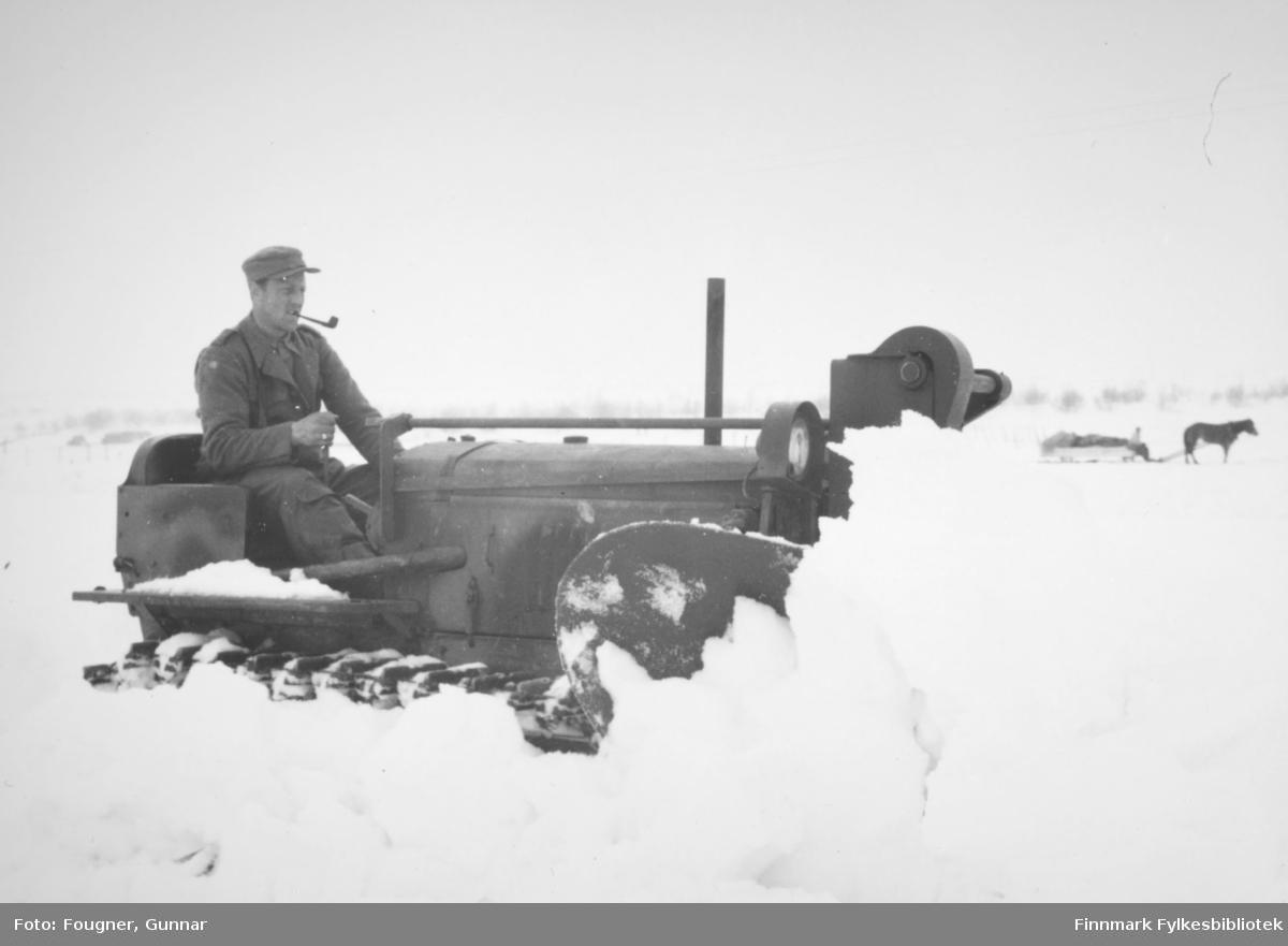 Snørydding med en beltebil/brøytebil. Politisoldat i uniform og med pipe.