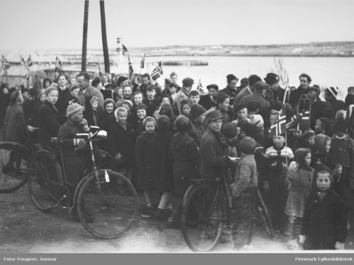 8. mai 1945 i Vadsø. En gruppe barn og voksne. De har pynta og har norske flagg.