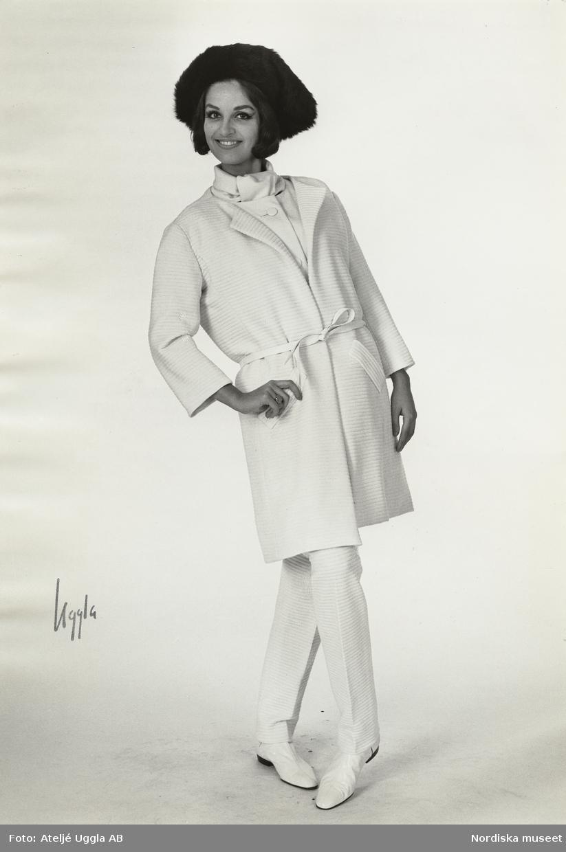 Modell i kappa och byxor i vit jersey, platta skor och hatt. NK:s Franska, original från Courrèges, höst.