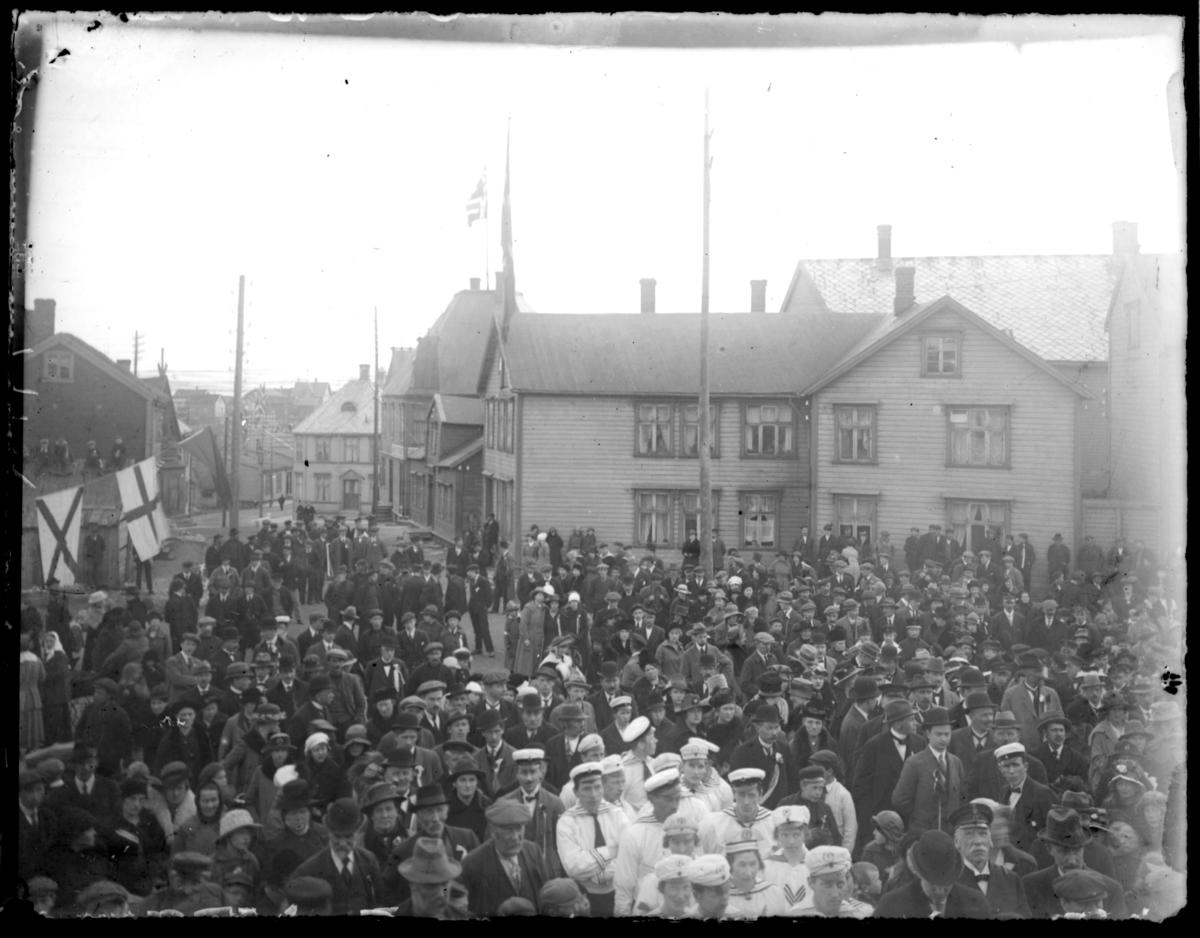 Antakelig 17. maifeiring i Vardø det flagges og en stor folkemengde er samlet. Midt i bildet en gruppe kledd i hvite uniformer, det ser ut til å være et sangkor