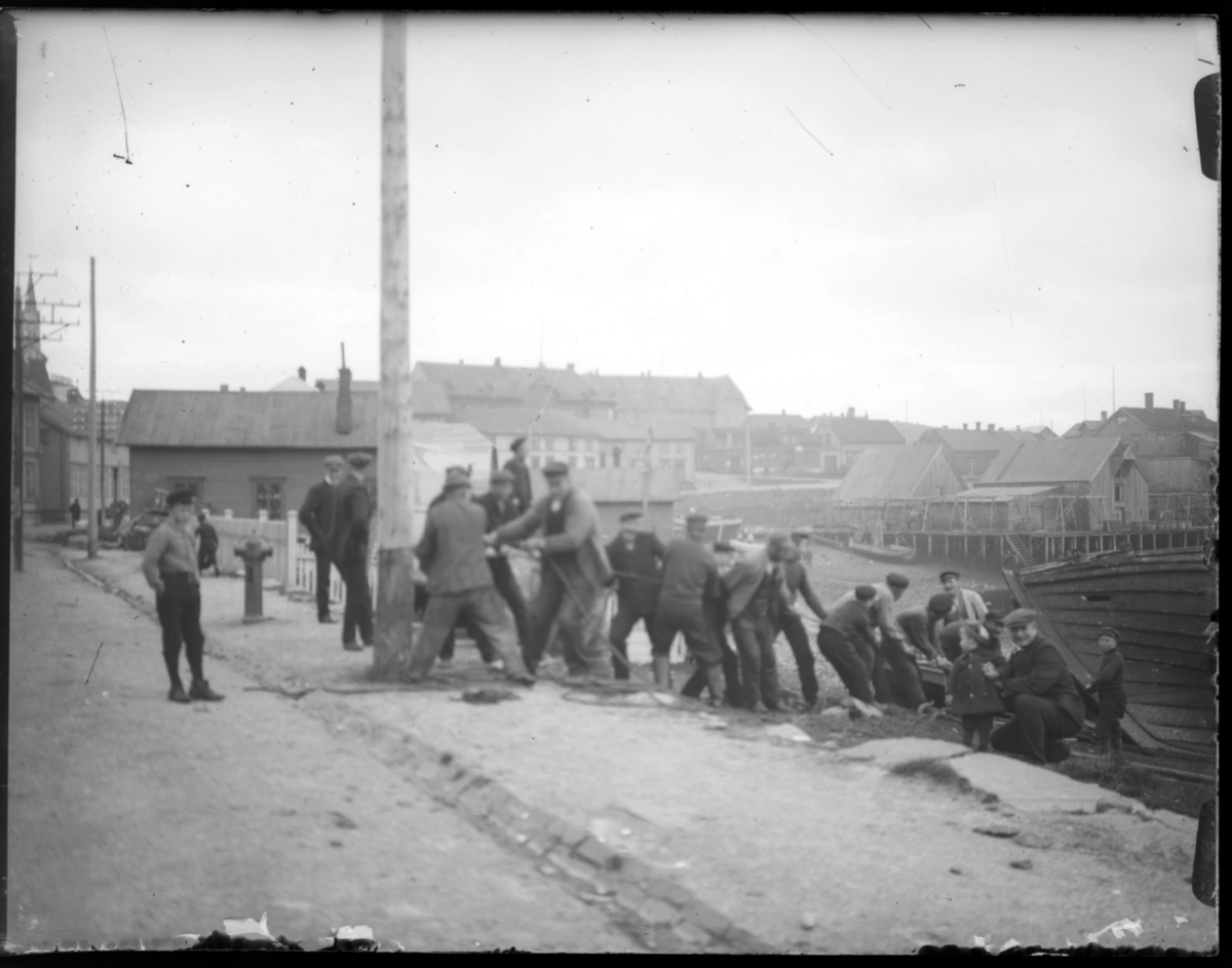 En båt dras opp på land på Valen i Vardø. Flere menn jobber sammen, og i bakgrunnen ser vi kirka og skolen i byen