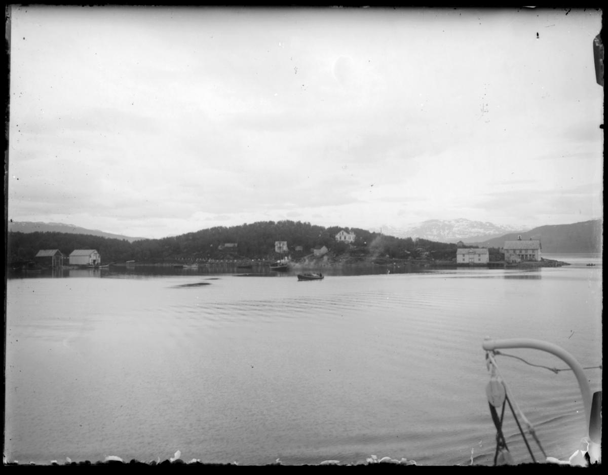 Bildet er tatt fra båt og vi ser en øy (?) med noen hus og sjøboder. Det er trær på øya og snøkledte fjell i bakgrunnen. Bildet kan være fra reisen nordover i 1912. Det ser ikke ut til å være fra Finnmark