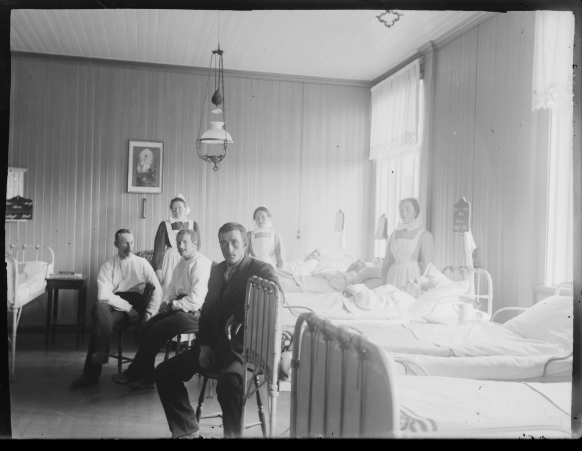 Inne på sykehuset i Vardø. Tre pasienter ligger i sengene. Tre menn sitter på krakker. Tre diakonisser (sykepleiere) står ved sengene. Det henger en lampe i taket og religiøse bilder på veggene. Også et termometer på veggen