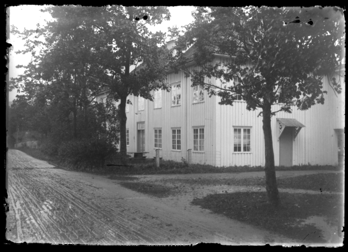 Fra stevne i Kristiansund. Et hus omgitt av høye trær.