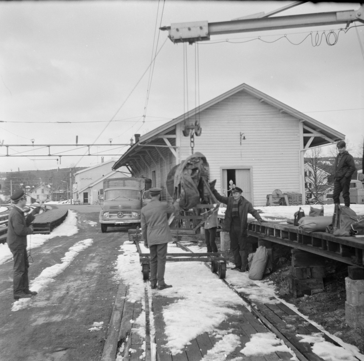 Godshuset på Sørumsand stasjon. En kappsag lastes over på jernbanetralle.