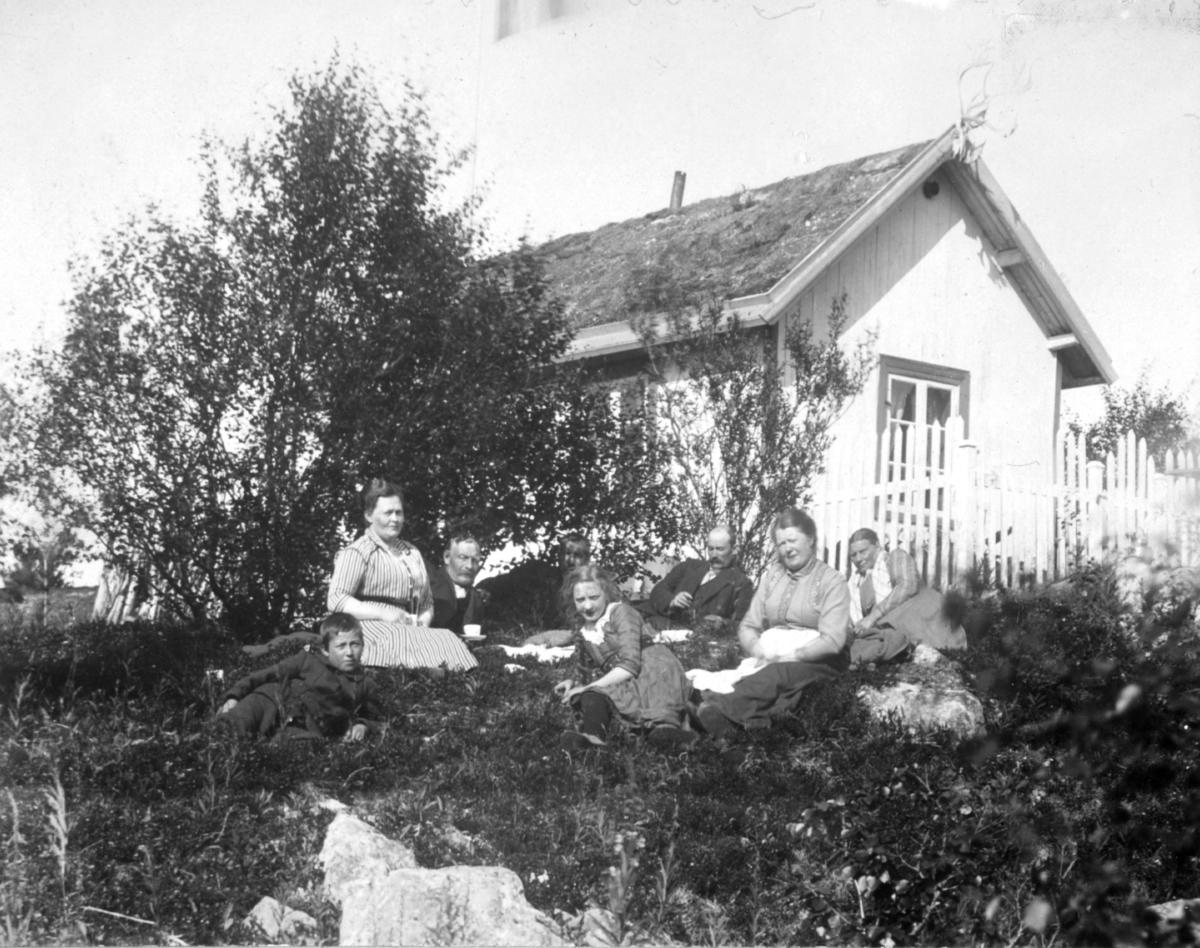 Damer, menn og barn sitter på bakken nedenfor hytta.