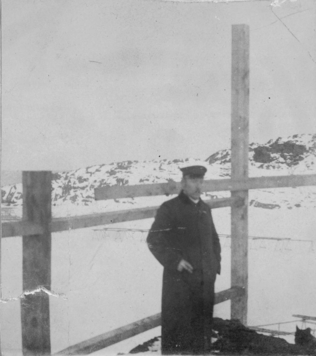 Karl Ohlsen i hatt og frakk. Han står ved noen stolper eller gjerde. Det er snø på marka.