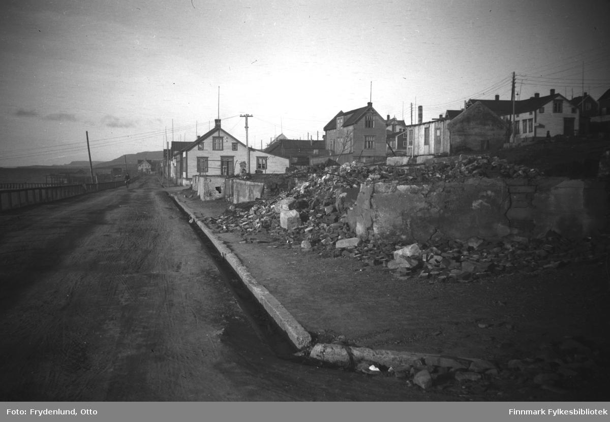 Havnegata i Vadsø fotografert mot øst. Vi ser bolighus som overlevde andre verdenskrig, og i forgrunnen på bildet krigsruiner. Det lyse huset midt på bildet tilhørte familien Dahl