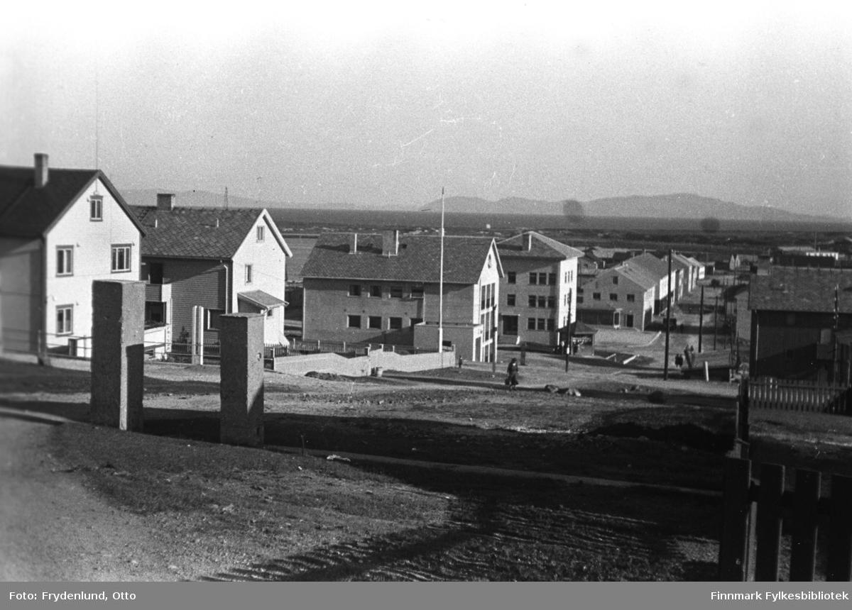 Gjenreiste sentrumsbygninger i Vadsø fotografert nedover Tollbugata mot torget. Hus nr. 3 og 4 på venstre side av veien er Vadsø sparebank og Vadsø rådhus, sistnevnte med en liten paviljong utenfor