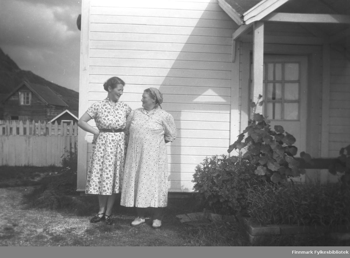 Fra venstre: Karen og Kathinka Mikkola, fotografert foran inngangen til våningshuset på gården Mikkelsnes i Neiden. Foran trappa ser vi frodige sommerblomster
